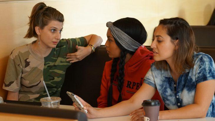 Tres amigas sentadas en un restaurante viendo el celular y hablando