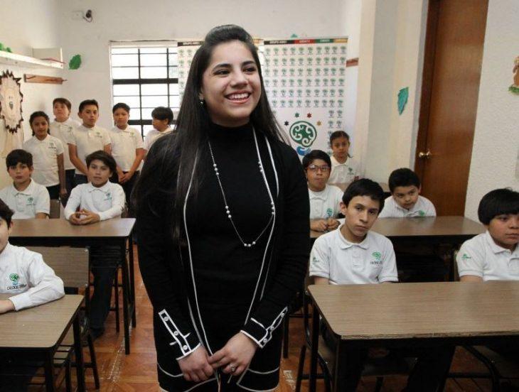 chica con brazos cruzados en un salón de clases