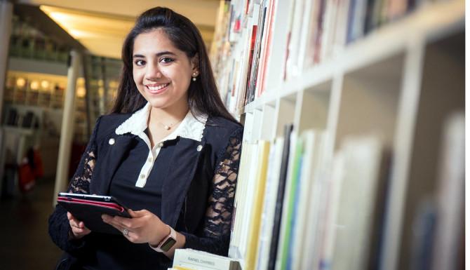 chica leyendo libros en una biblioteca