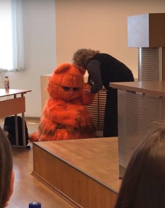 Alumno asiste a clase disfrazado del gato Garfield y la maestra no puede evitar acariciarlo