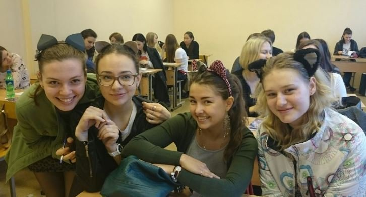 Alumnas en el salón de clases con diademas de orejas de gato