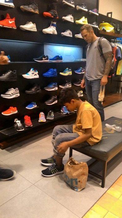 Niño de la calle midiéndose zapatos que un turista le regaló