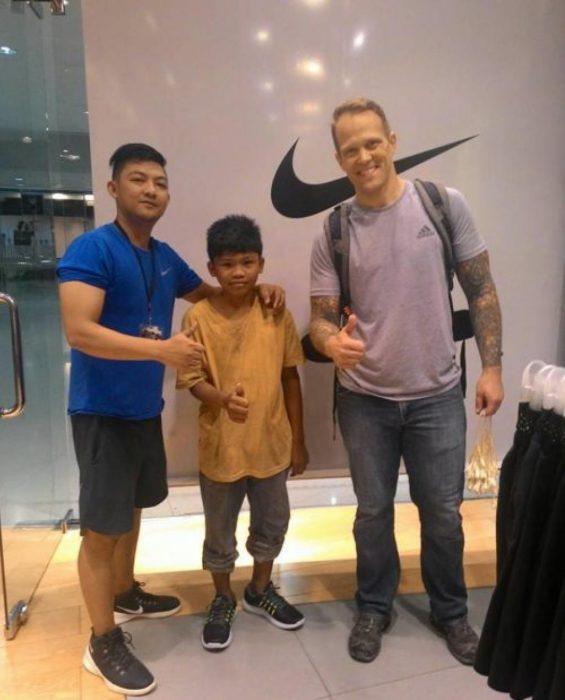 Niño de la calle junto a turista y empleado de una tienda de zapatos