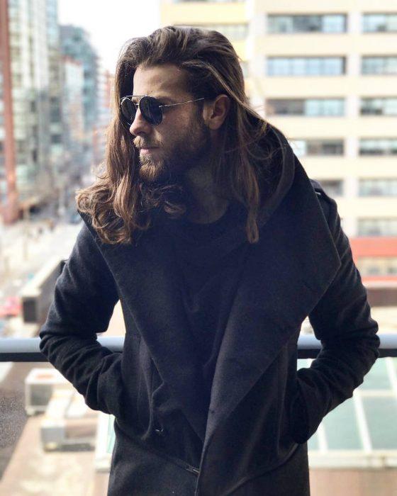 Hombre con barba y cabello largo usando lentes para sol y abrigo