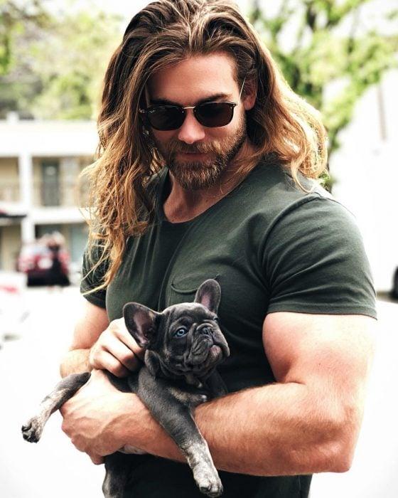 Hombre musculoso de cabello largo y barba cargando a un perro