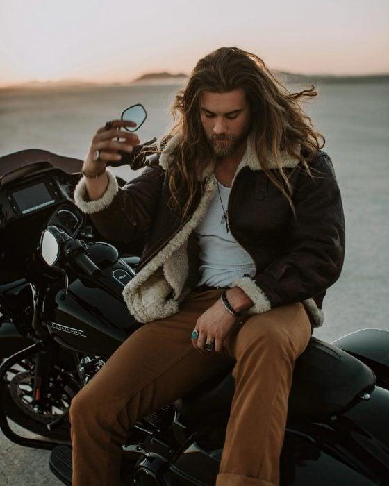 Hombre de cabello largo y barba encima de una motocicleta