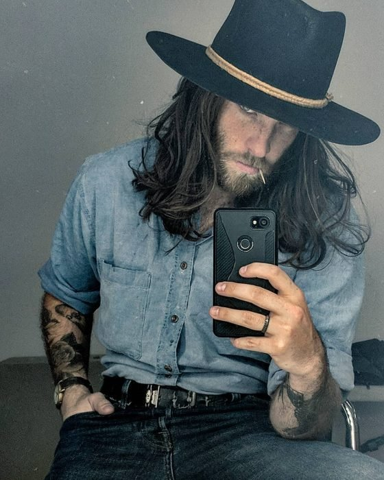 Hombre con cabello largo y barba usando sombrero y tatuajes en los brazos