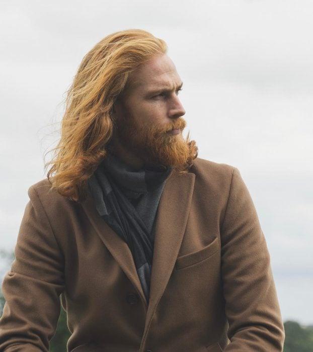 Hombre pelirrojo con barba y cabello largo usando un abrigo café