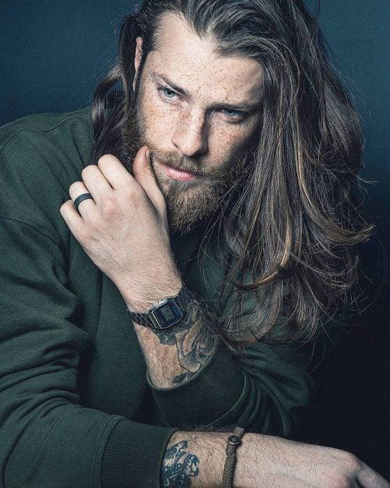 Hombre de cabello largo con barba, ojos azules y tatuajes en los brazos