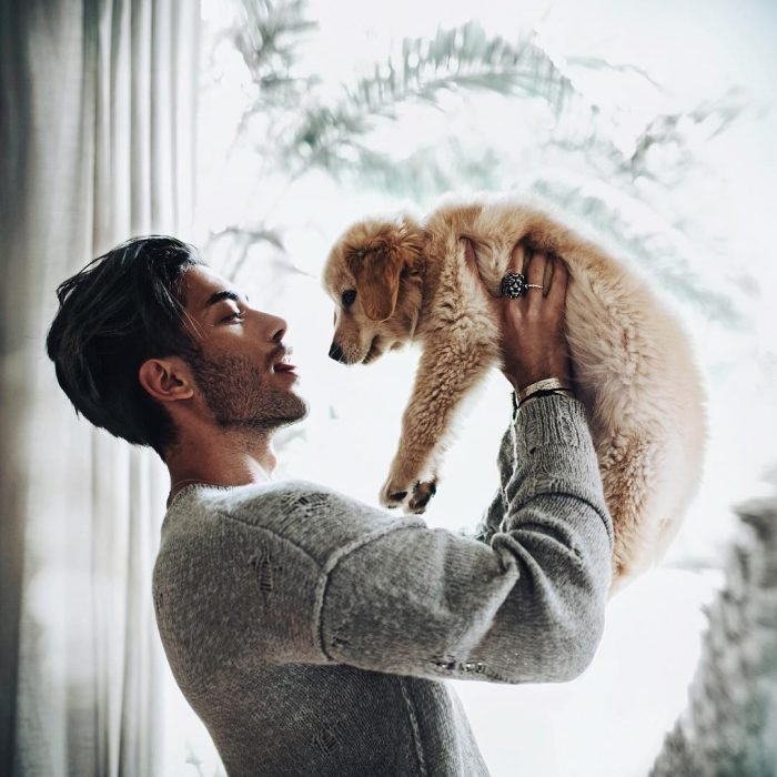 Hombre de cabello negro y barba cargando a un perrito café
