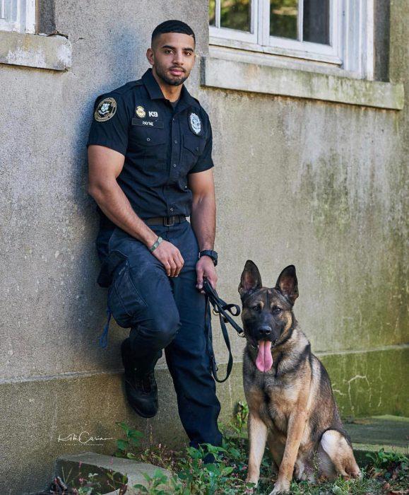 Oficial de policía con uniforme junto a un perro pastor alemán