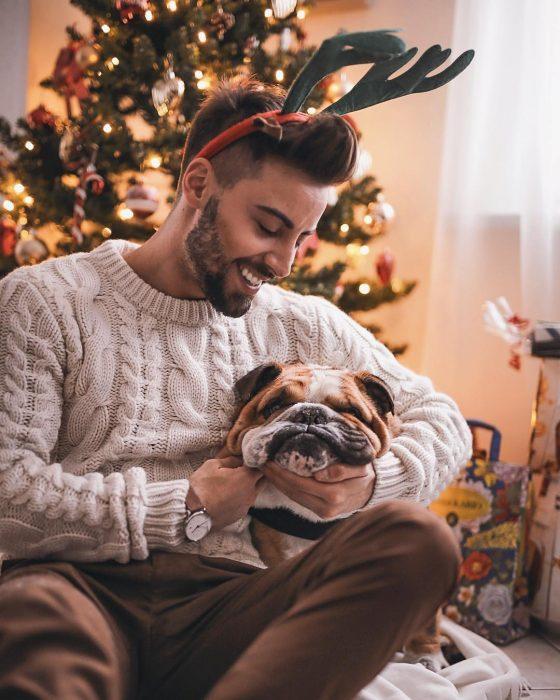 Hombre con cuernos de reno abrazando a un perro bulldog inglés