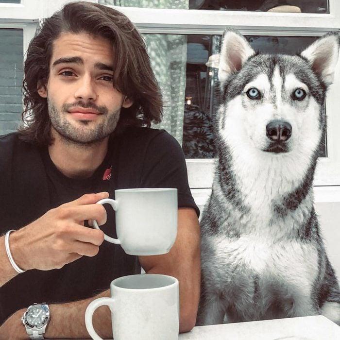 Hombre de cabello largo bebiendo café a lado de un perro husky