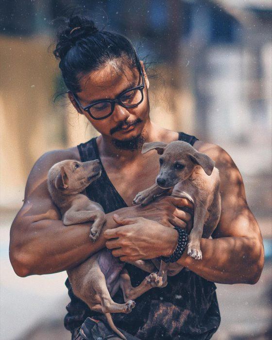 Hombre de cabello largo con chongo cargando a dos perros cafés