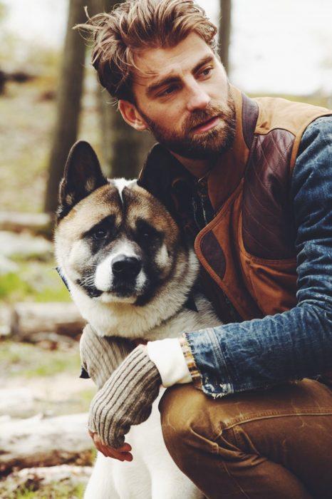 Hombre rubio con barba abrazando a un perro