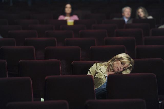 mujer rubia dormida en sala de cine