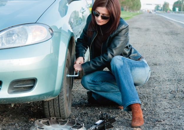 chica cambiando la llanta de su auto