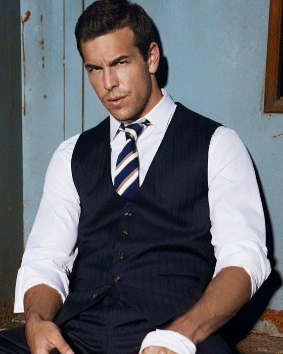 Hombre con camisa blanca, corbata y chaleco azul