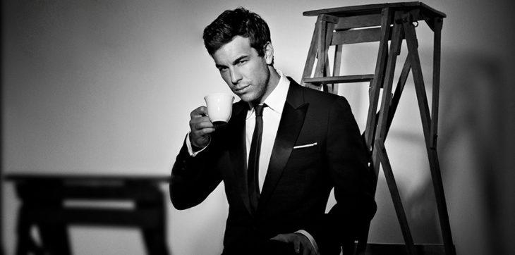 Fotografía de hombre en blanco y negro con traje bebiebdi café