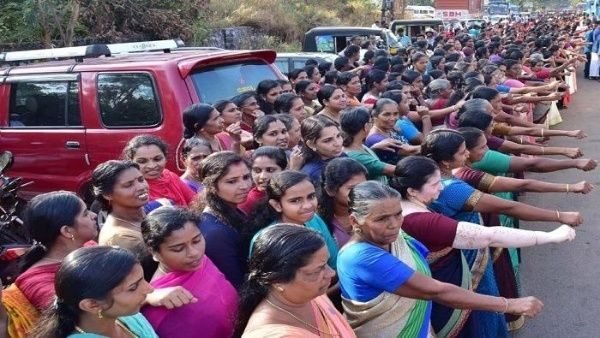 mujeres formadas en una fila alzando sus brazos