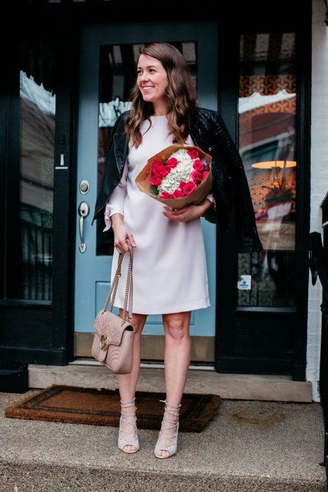 Mujer con vestido blanco y chaqueta de cuero con ramo de flores