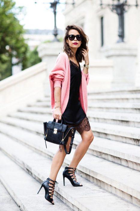 Mujer de cabello castaño con vestido de seda y encaje con abrigo rosa