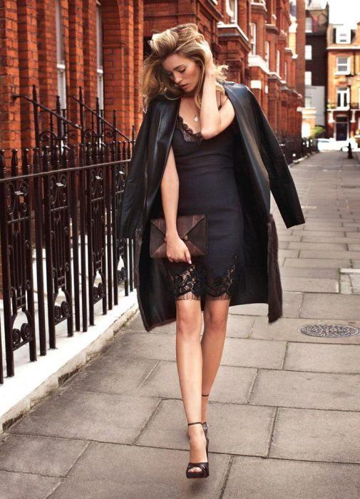 Mujer rubia con vestido de seda negro ajustado y una chaqueta