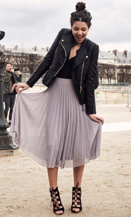 Chica con falda midi de tablas y chaqueta de cuero