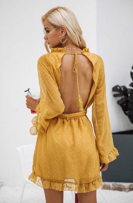 Mujer rubia con vestido amarillo con escote en la espalda y aretes de corazón