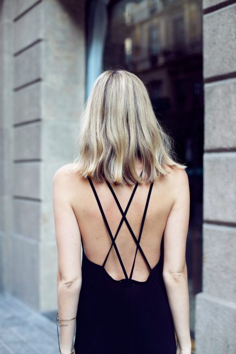 Mujer rubia con vestido negro y escote en la espalda