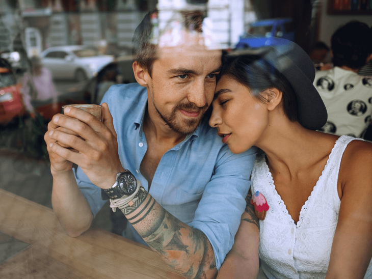 Pareja de novios con tatuajes tomando café