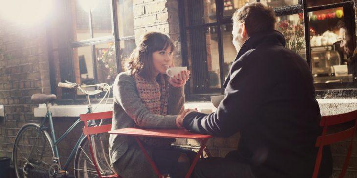Pareja de novios platicando mientras beben café