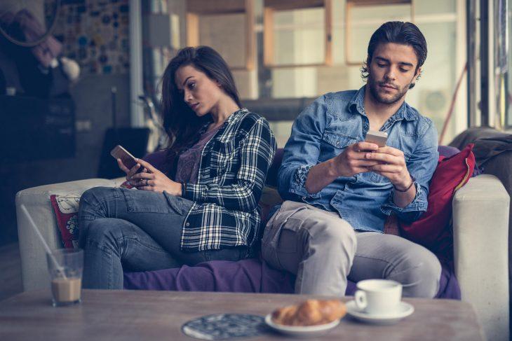 Pareja sentada en el sillón dándose la espalda y viendo sus celulares