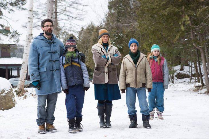 Familia jugando en la nieve durante invierno