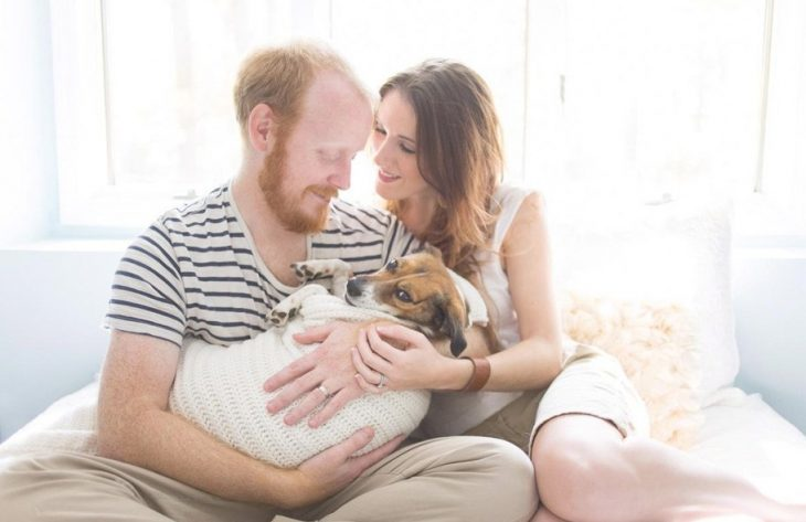 pareja cargando a un perro como si fuera un bebé