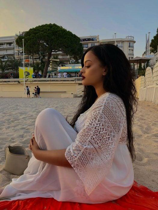 Mujer afroamericana con cabello largo y vestido blanco sentada en la playa que se parece a Rihanna
