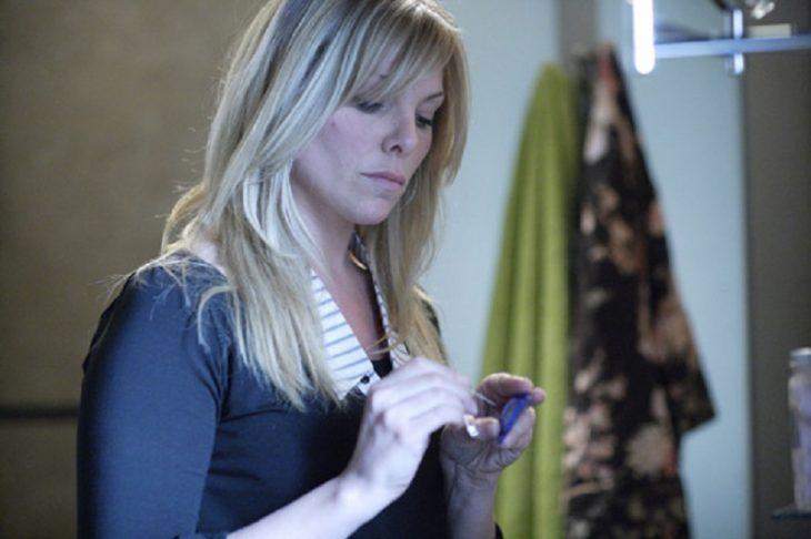 Mujer rubia de blusa morada pinchando un condón