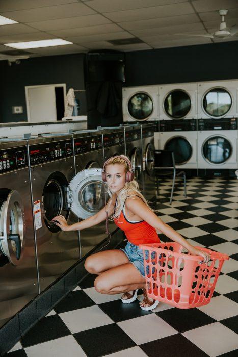 Mujer rubia en una lavandería lavando su ropa sucia