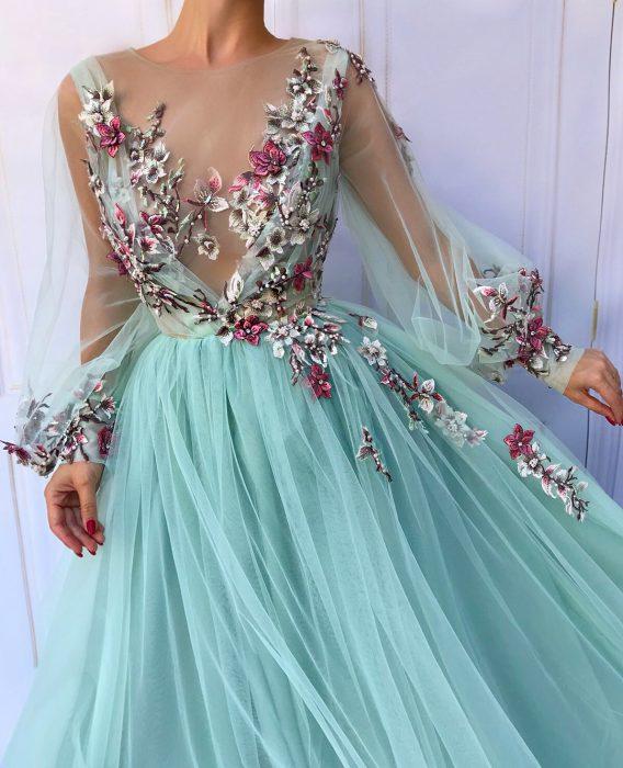 Vestido en corte A, color azul con mangas de tul y adornos de flores rosas y blancas