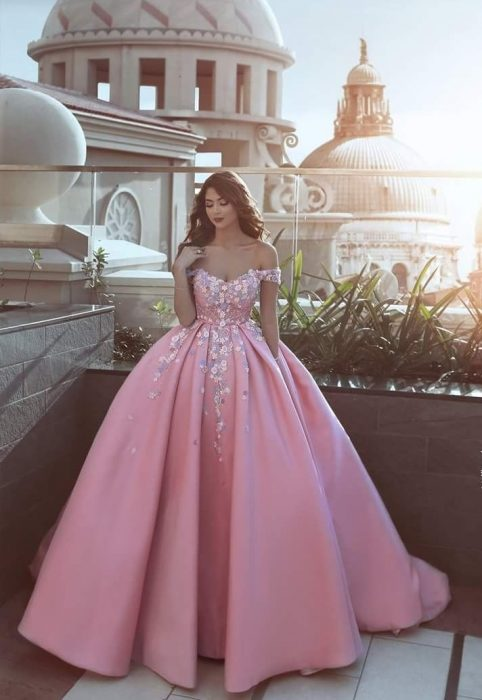Chica con vestido para XV años rosa de corte princesa y con adornos de flores