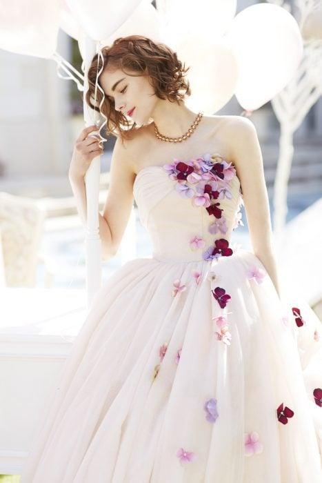 Chica con vestido para XV años de corte princesa color perla con flores