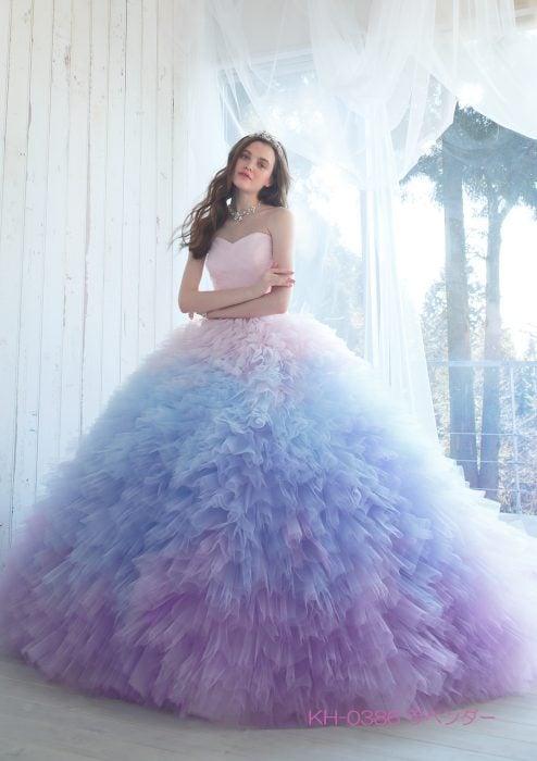 Chica con vestido para XV años de corte princesa con olanes de color rosa degradado a morado