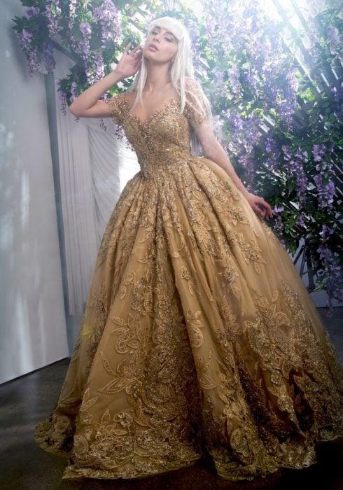 Chica con vestido para XV años de corte princesa dorado con encaje de flores