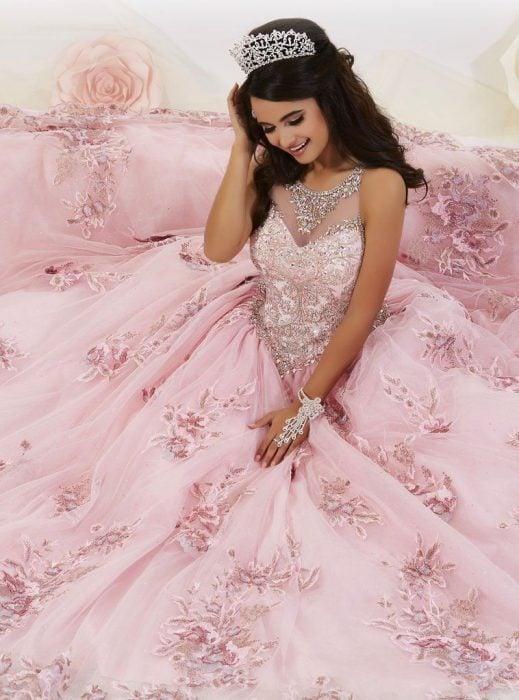 Chica con vestido para XV años de corte princesa colo rosa con pedrería y corona