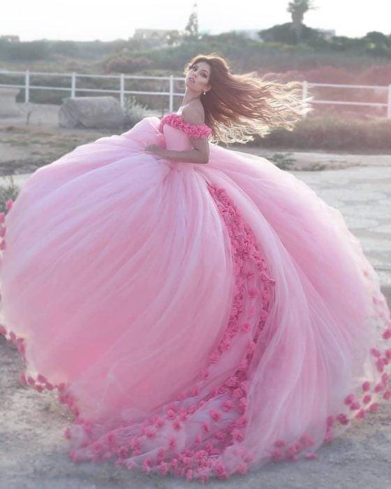 Chica con vestido para XV años de corte princesa color rosa con flores y tul