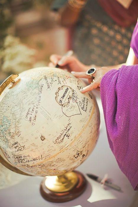 globo terraqueo y manos de mujer con anillo