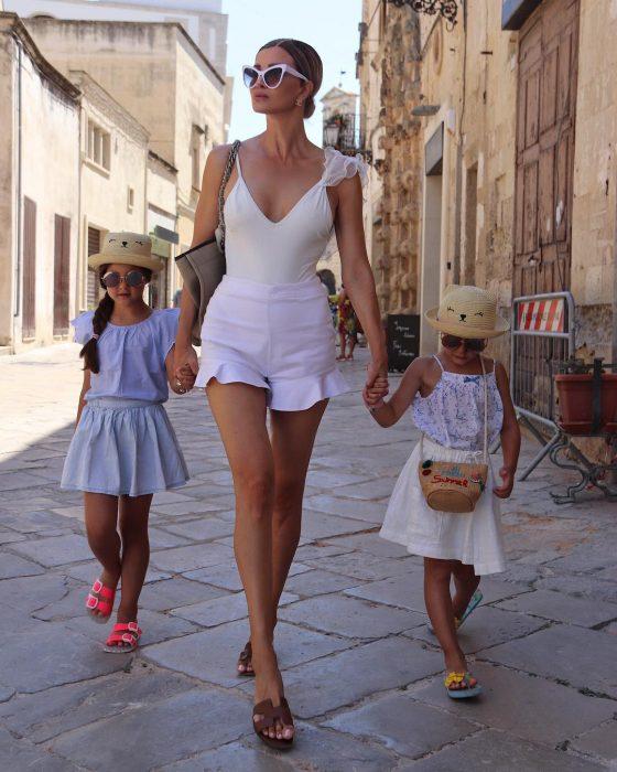 Abuela joven caminando tomada de la mano con sus nietas caminando en la calle