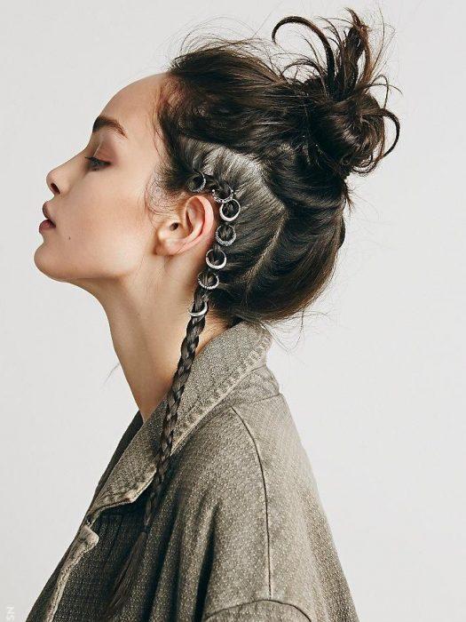 Chica de cabello castaño con trenza de lado y adornos