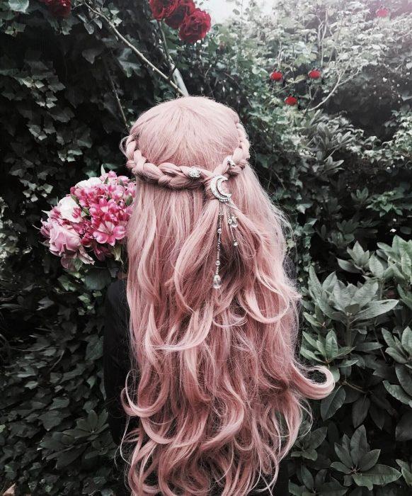 Chica de cabello rosa pastel, con trenza y con adornos