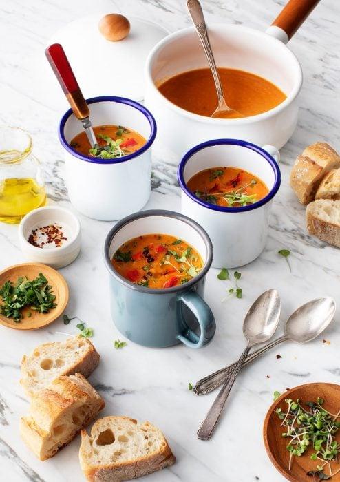 Un sartén con sopa de zanahoria y a lado tres tazas con la misma sopa